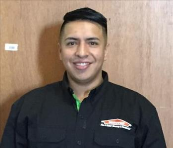 Male employee in a black logo SERVPRO jacket, posing