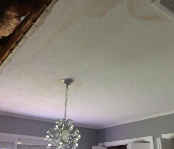 water stained ceiling, chandelier hanging and exposed attic area with insulation showing
