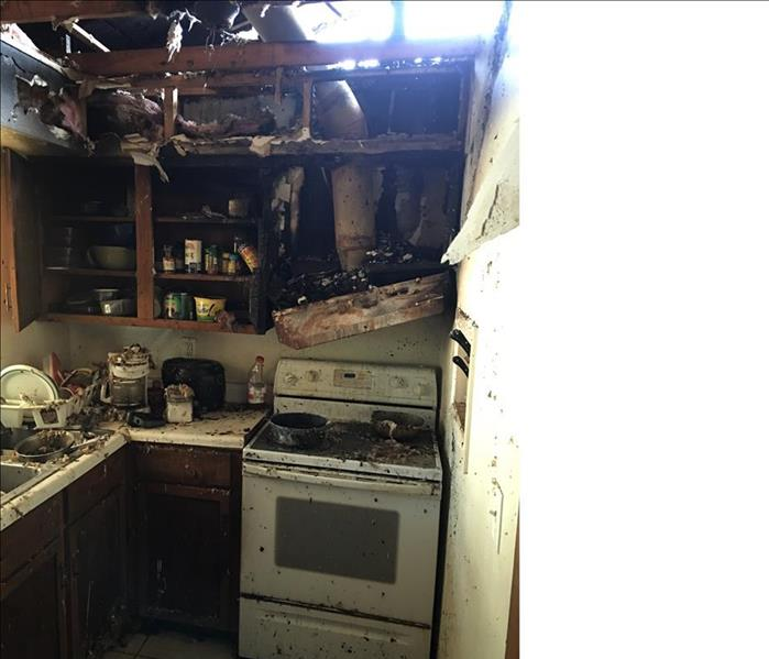 fire damaged in a kitchen, debris, hole in the roof
