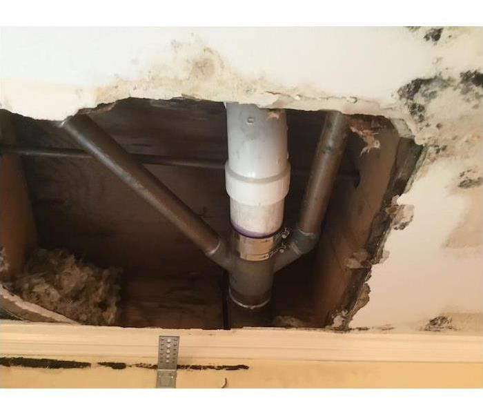 Wall with cut away sheetrock with pipe showing and mold