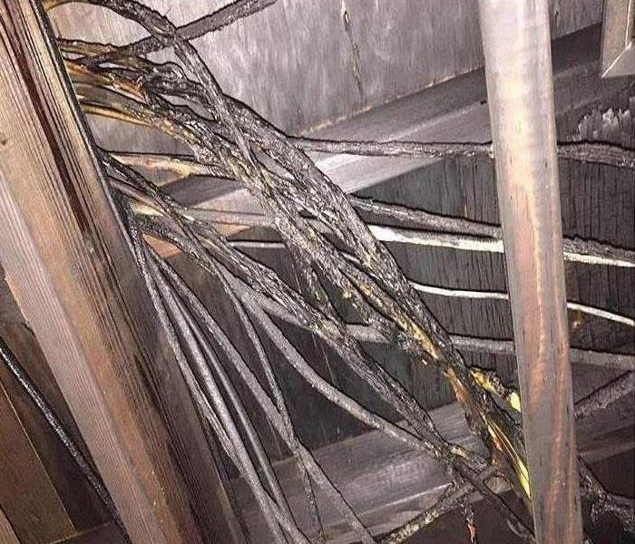 upward view of attic crawlspace blackened by fire with damaged electrical cables