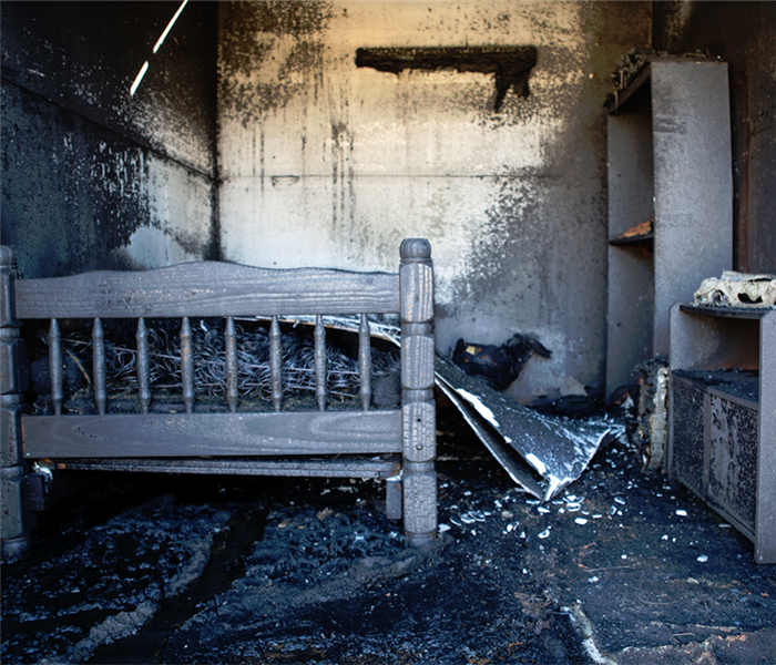 a fire damaged bedroom with soot covering everything