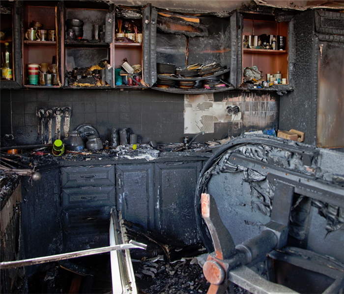 a fire damaged kitchen with soot and ashes everywhere